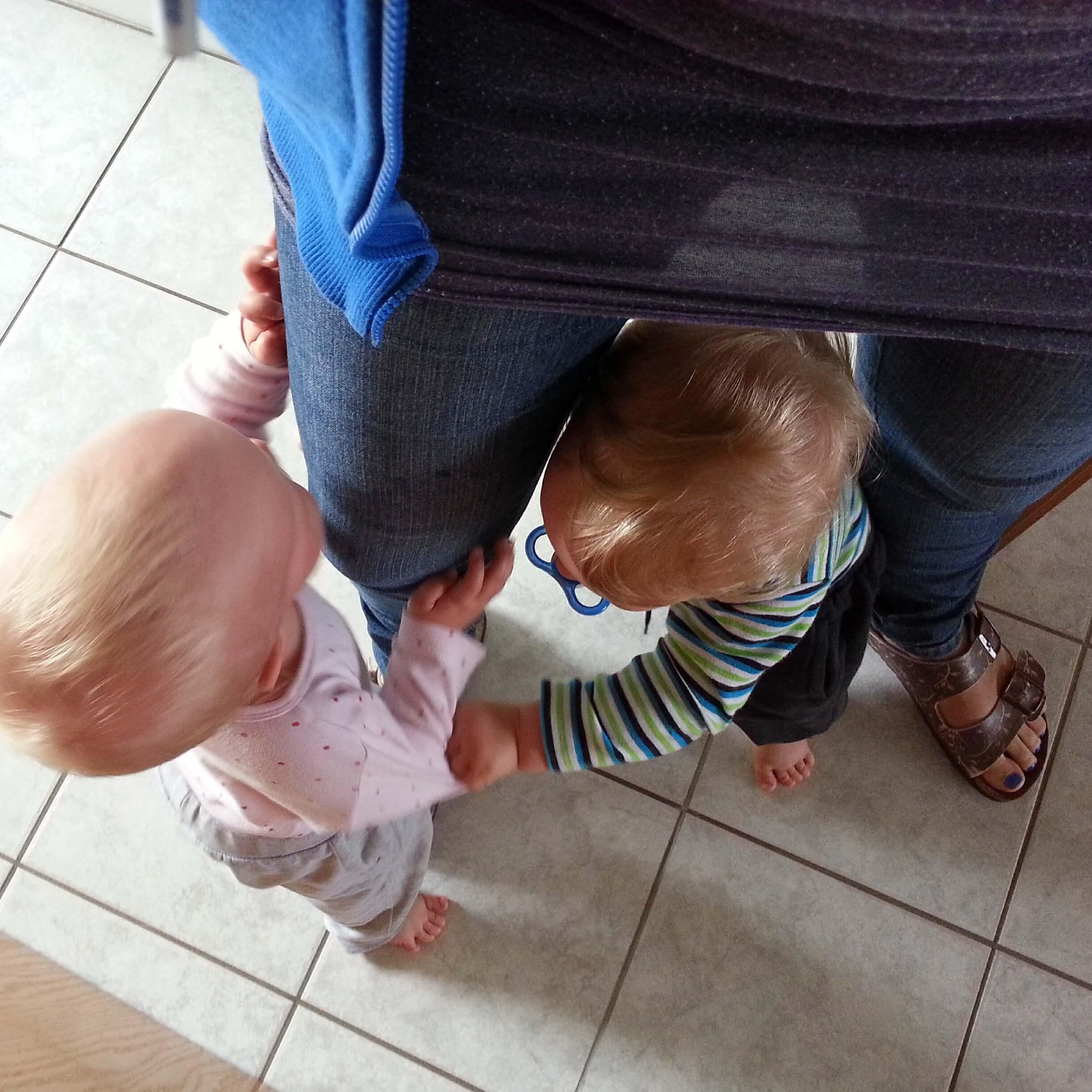 zwei Kleinkinder an Mamas Bein