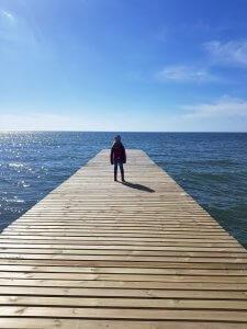 Kind auf Steg am Meer