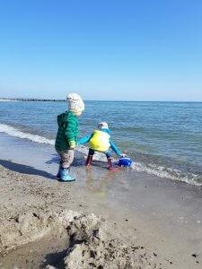 Kinder spielen in der Meeresbrandung