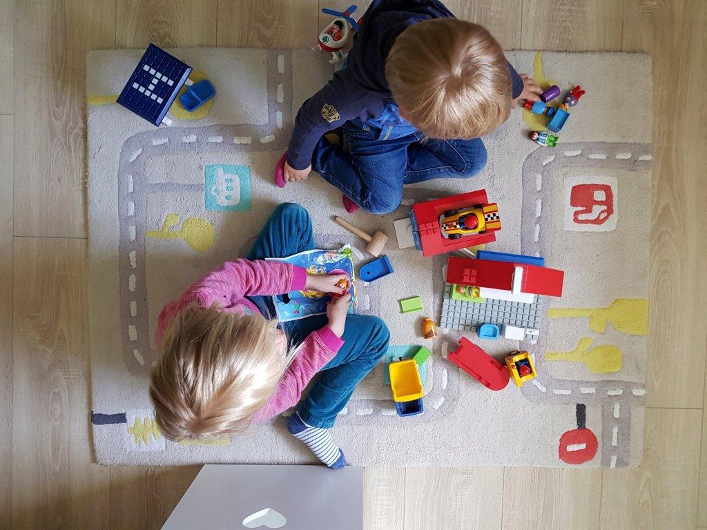 Spielende Kinder auf Spielteppich